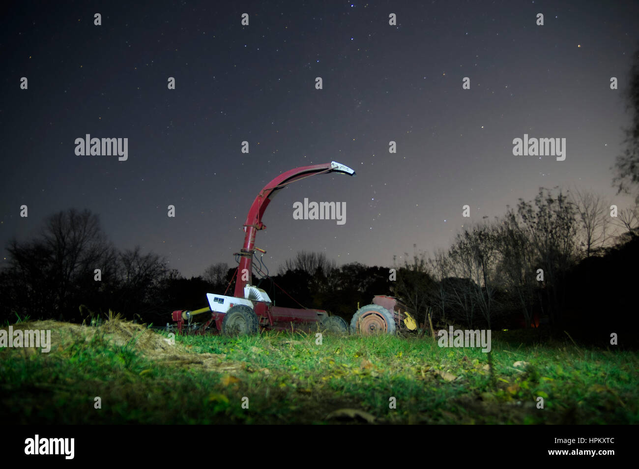 machinery agriculture silo under a clear starry night sky. - Stock Image