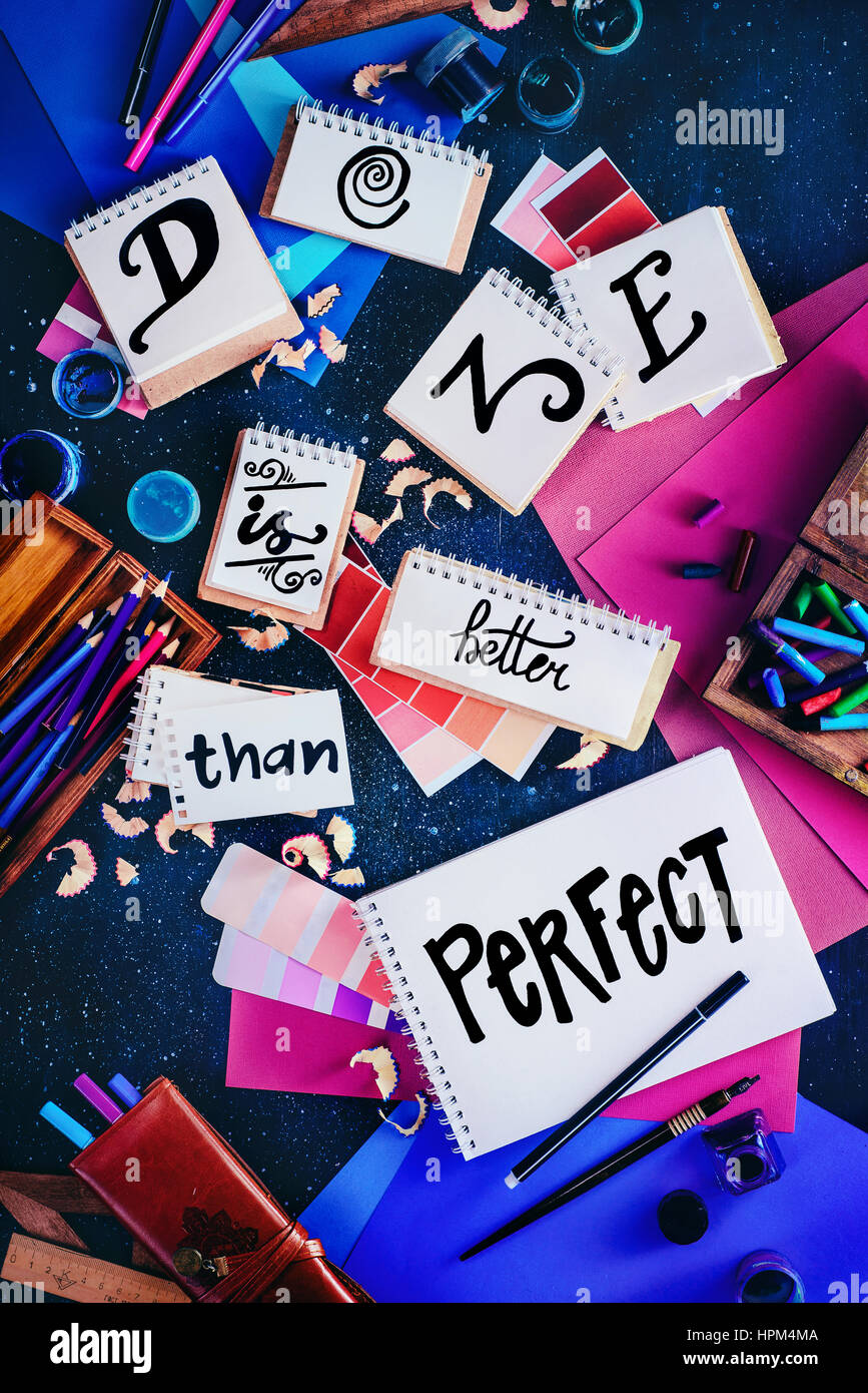 Quote lettering 'Done is Better than Perfect' on a variety of notepads with artist's tools - Stock Image