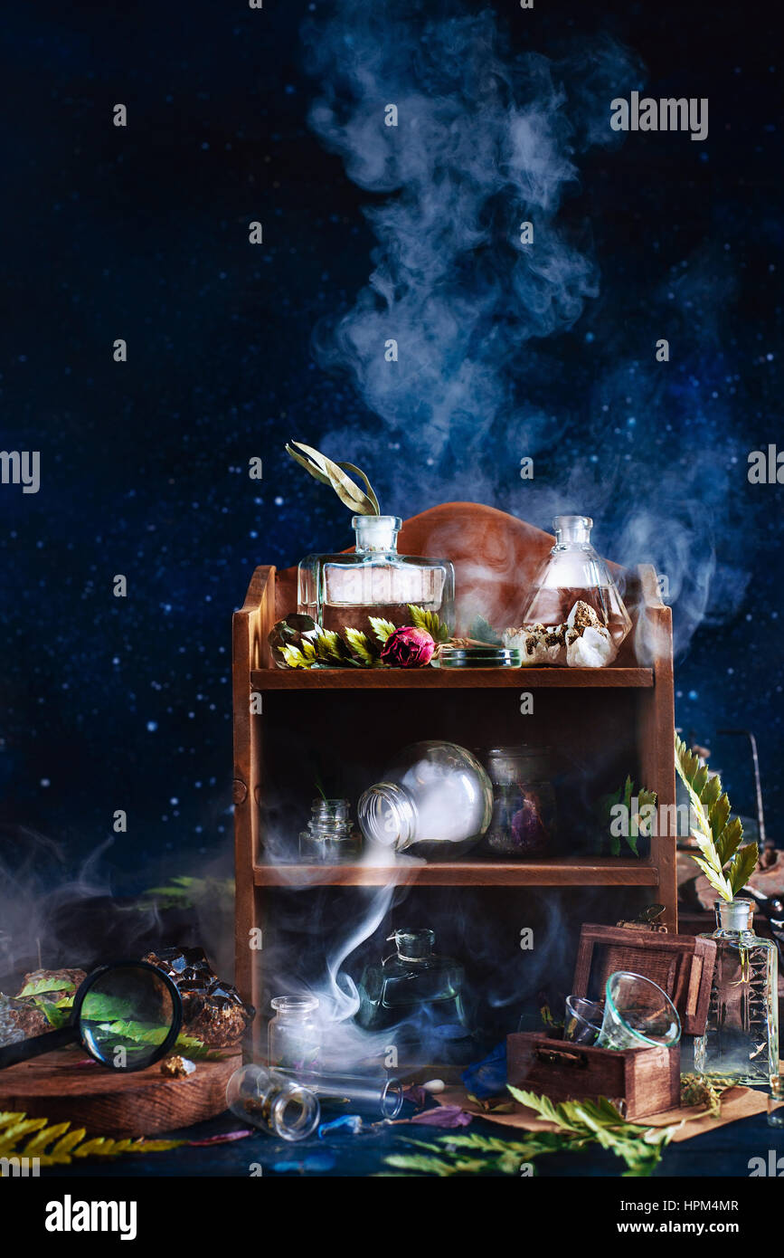 Still life with wooden box, bottles, stones, findings, trophies, magnifying glass and rising smoke - Stock Image