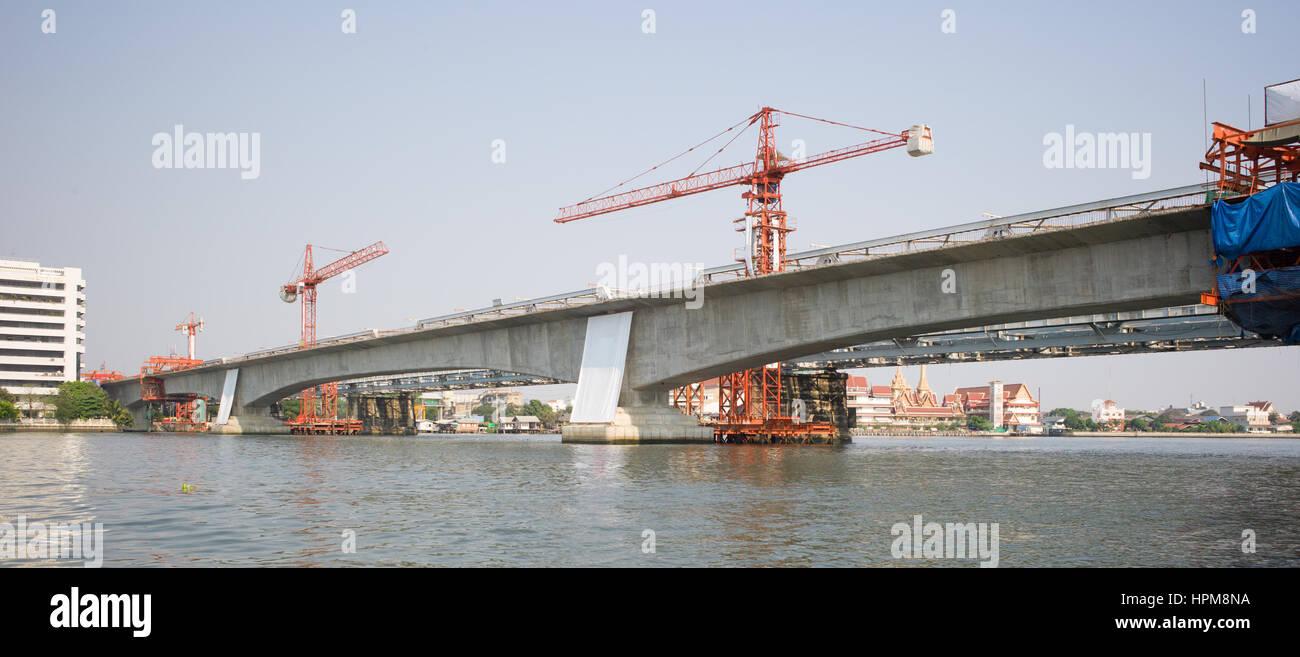 Reinforced concrete multi span bridge under construction across river, Bangkok, Thailand - Stock Image
