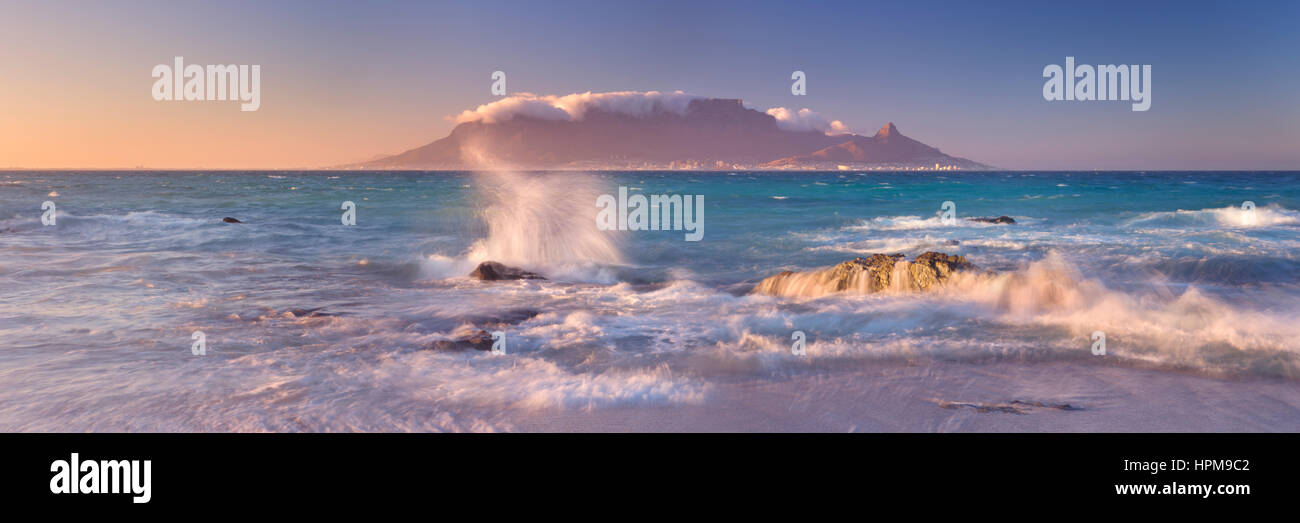 Sunrise over the Table Mountain and Cape Town from the beach of Bloubergstrand. - Stock Image