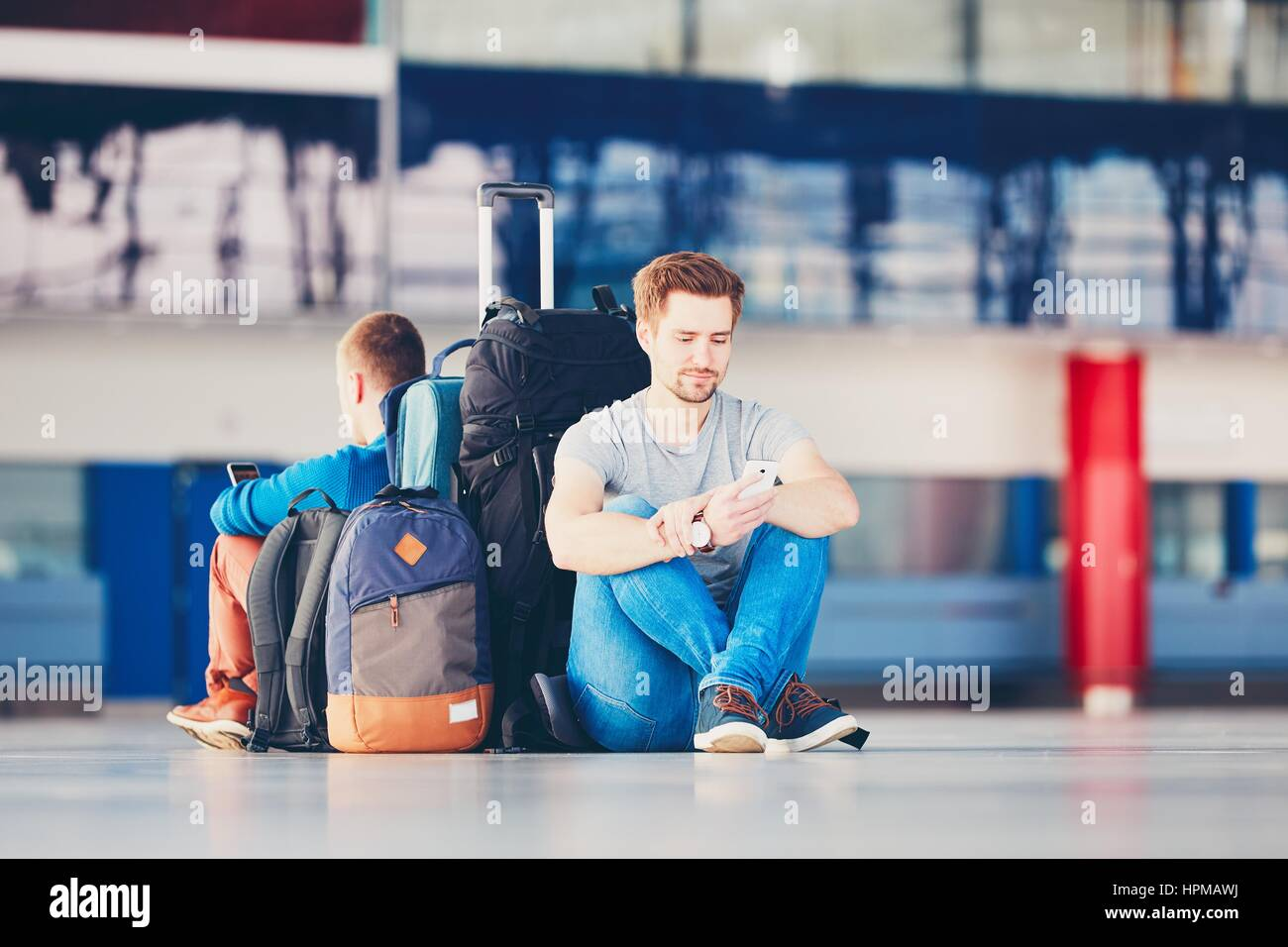 Two friends traveling together. Travelers with mobile phones waiting at the airport departure area for their delay - Stock Image