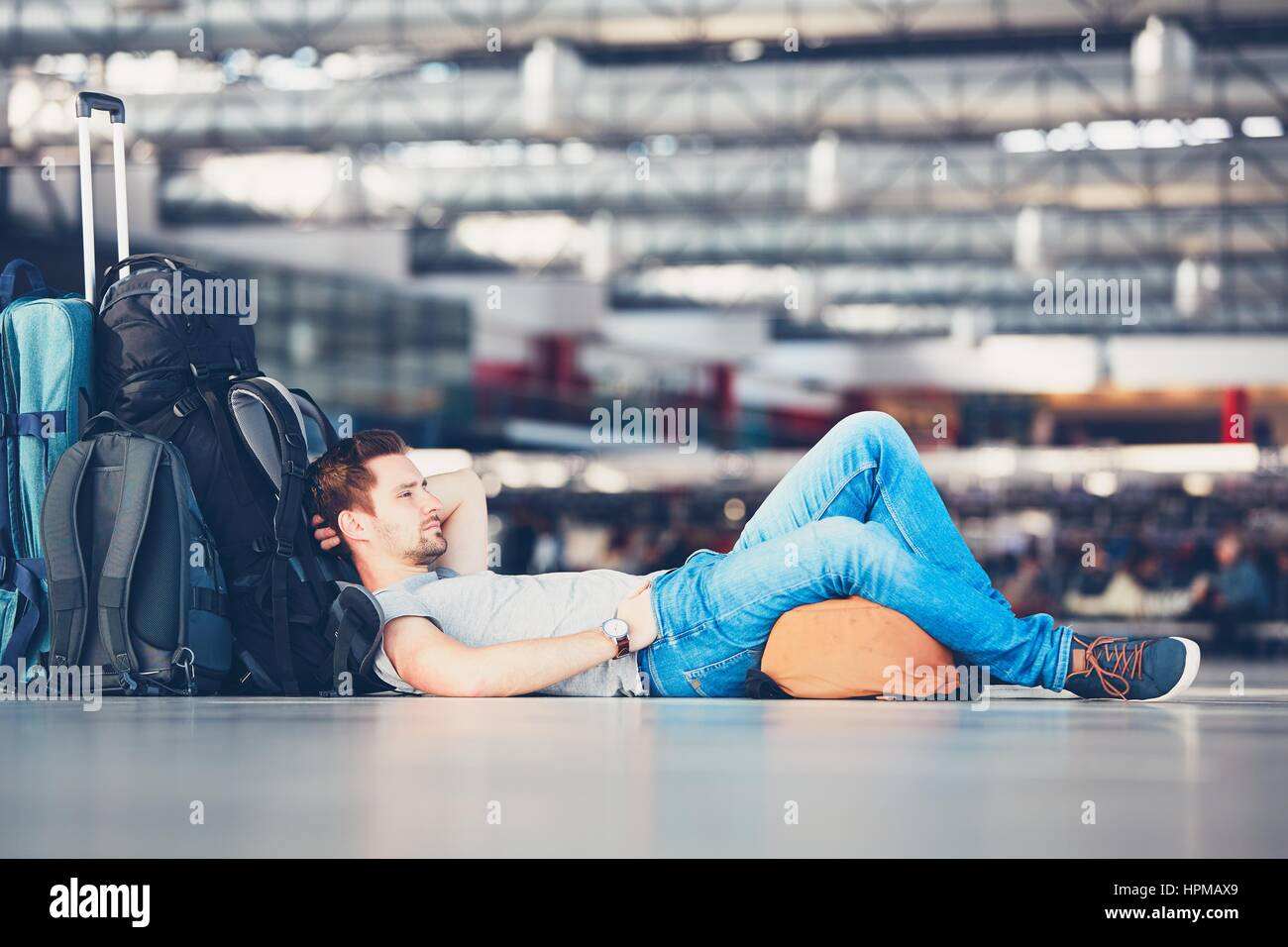 Traveler waiting at the airport departure area for his delay flight. - Stock Image