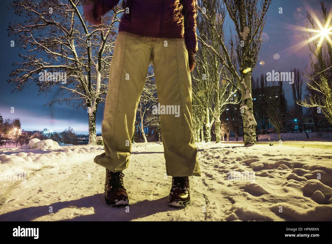 Human feet standing snowy road night street lamps - Stock Image