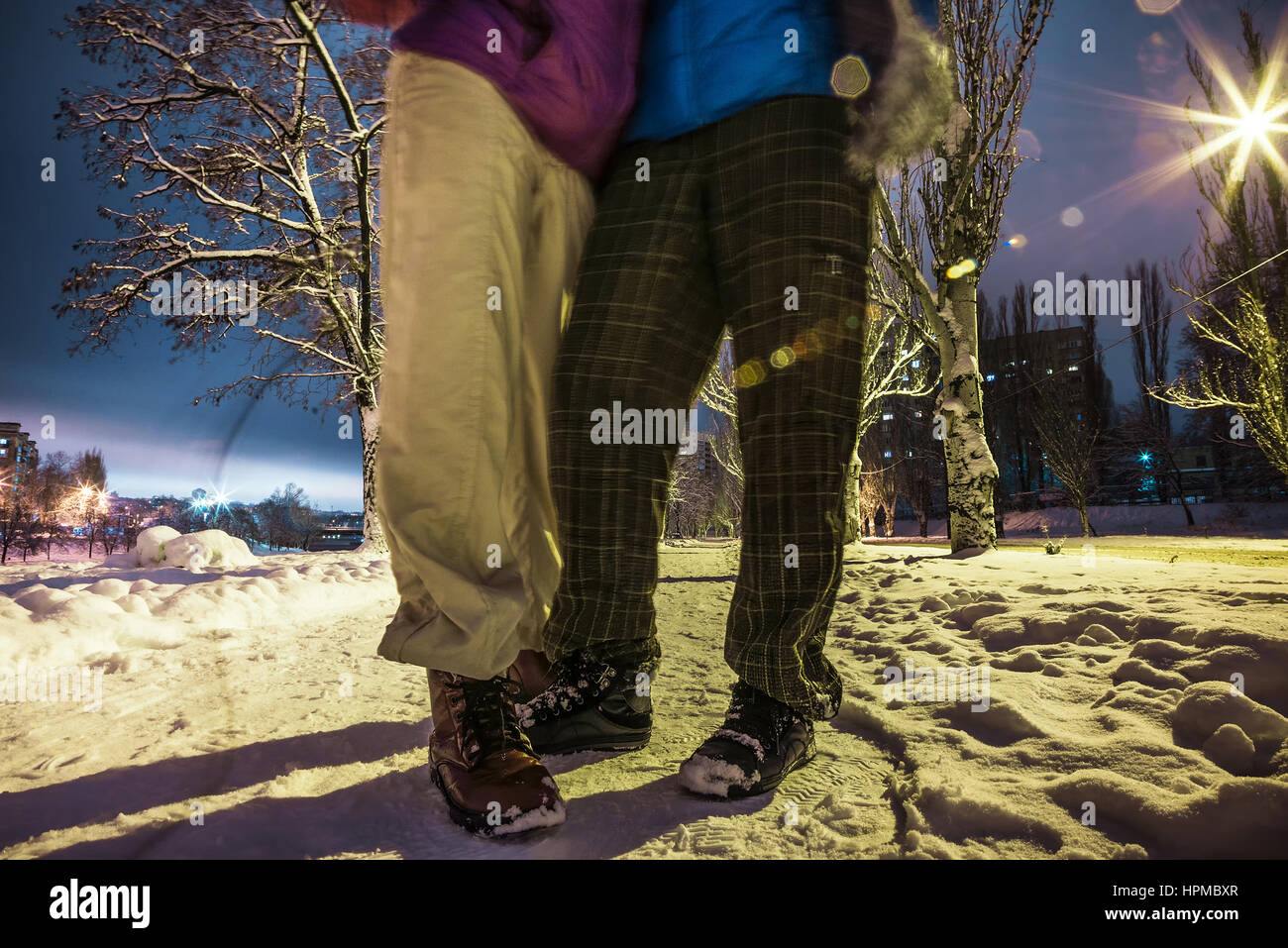 Two Human feet standing snowy road night street lamps - Stock Image