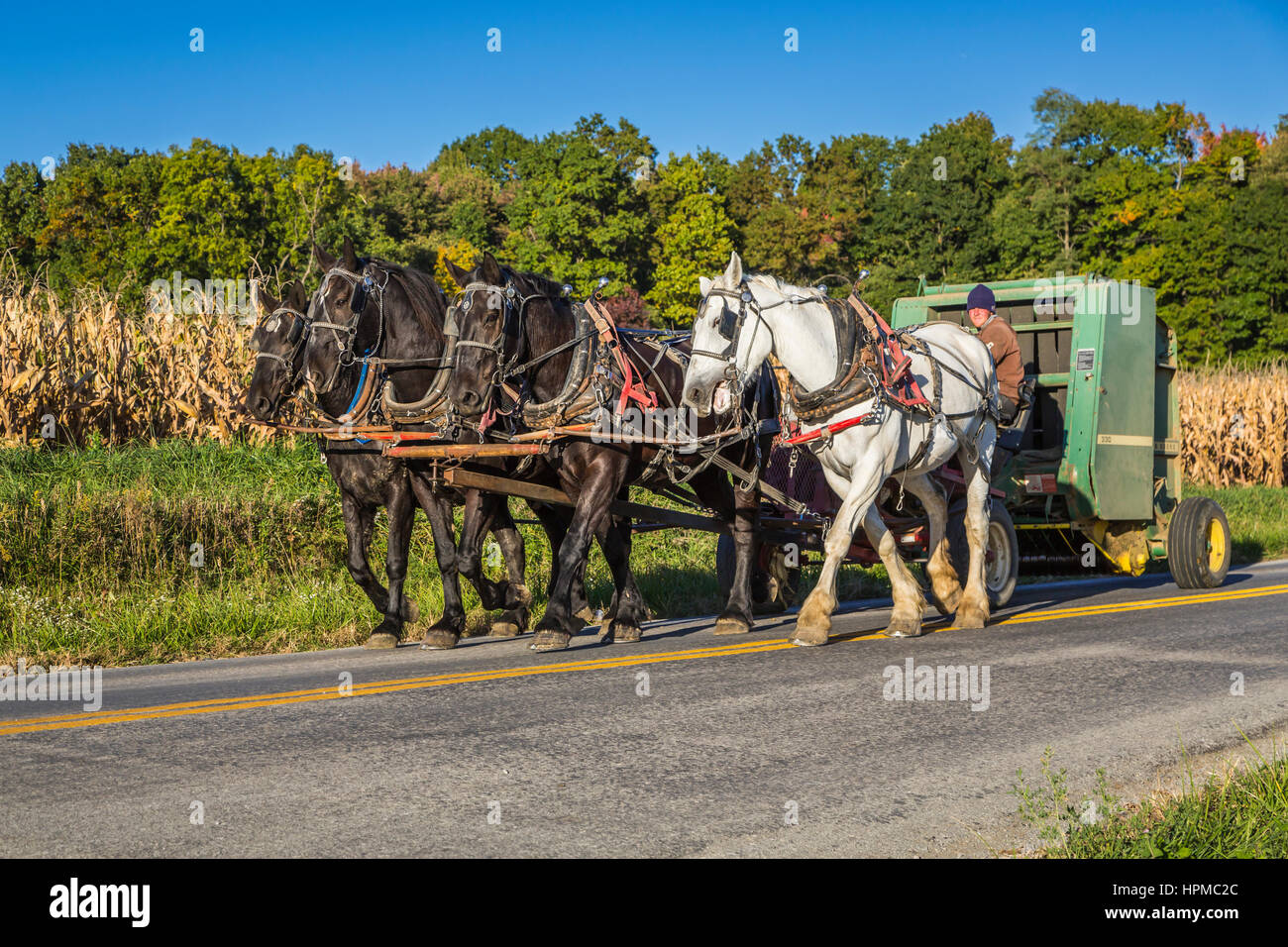 A horse drawn hay baler along the roadway in the countryside near Kidron, Ohio, USA. - Stock Image