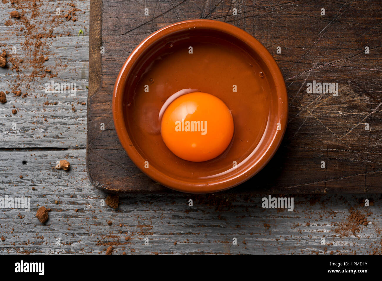 high-angle shot of an earthenware plate with a cracked chicken egg on a rustic wooden table - Stock Image