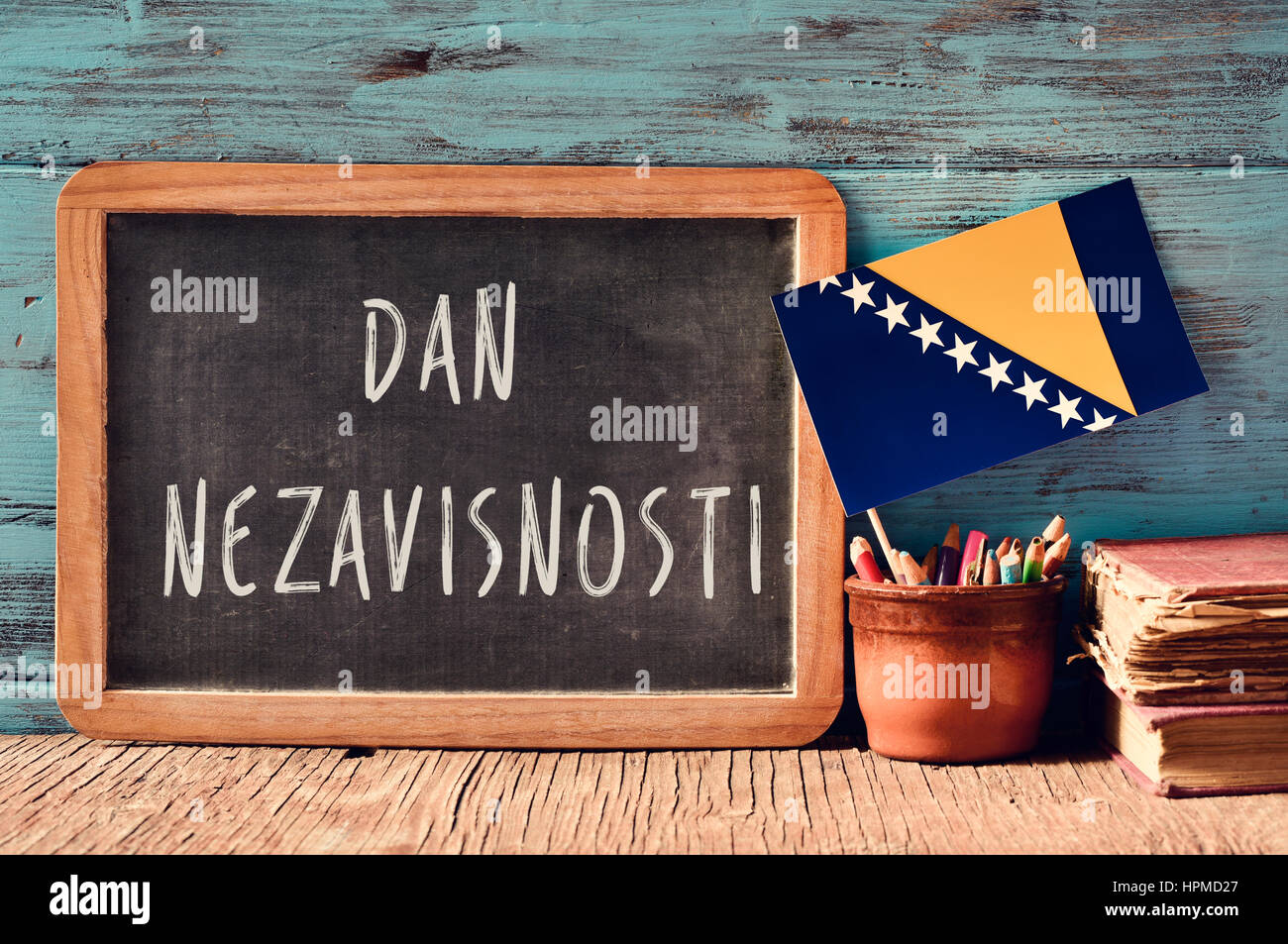 a chalkboard with the text Dan Nezavisnosti, Independence Day written in Bosnian, a pot with pencils, some books Stock Photo