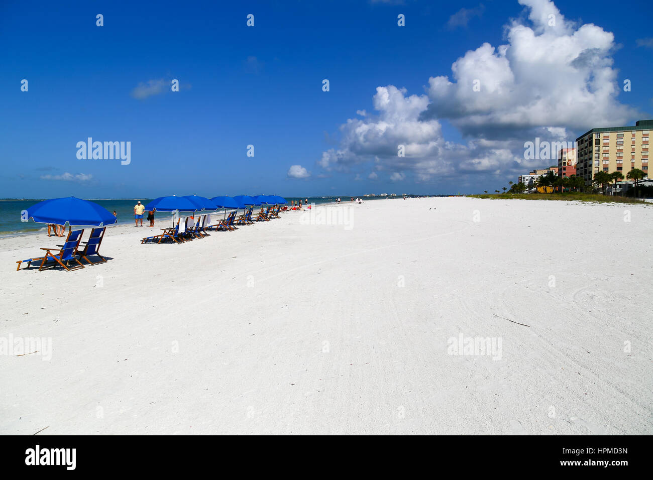 Fort Myers Beach, USA - May 12, 2015: Beach chairs and sunshades on the beach with apartment blocks and hotels on Stock Photo