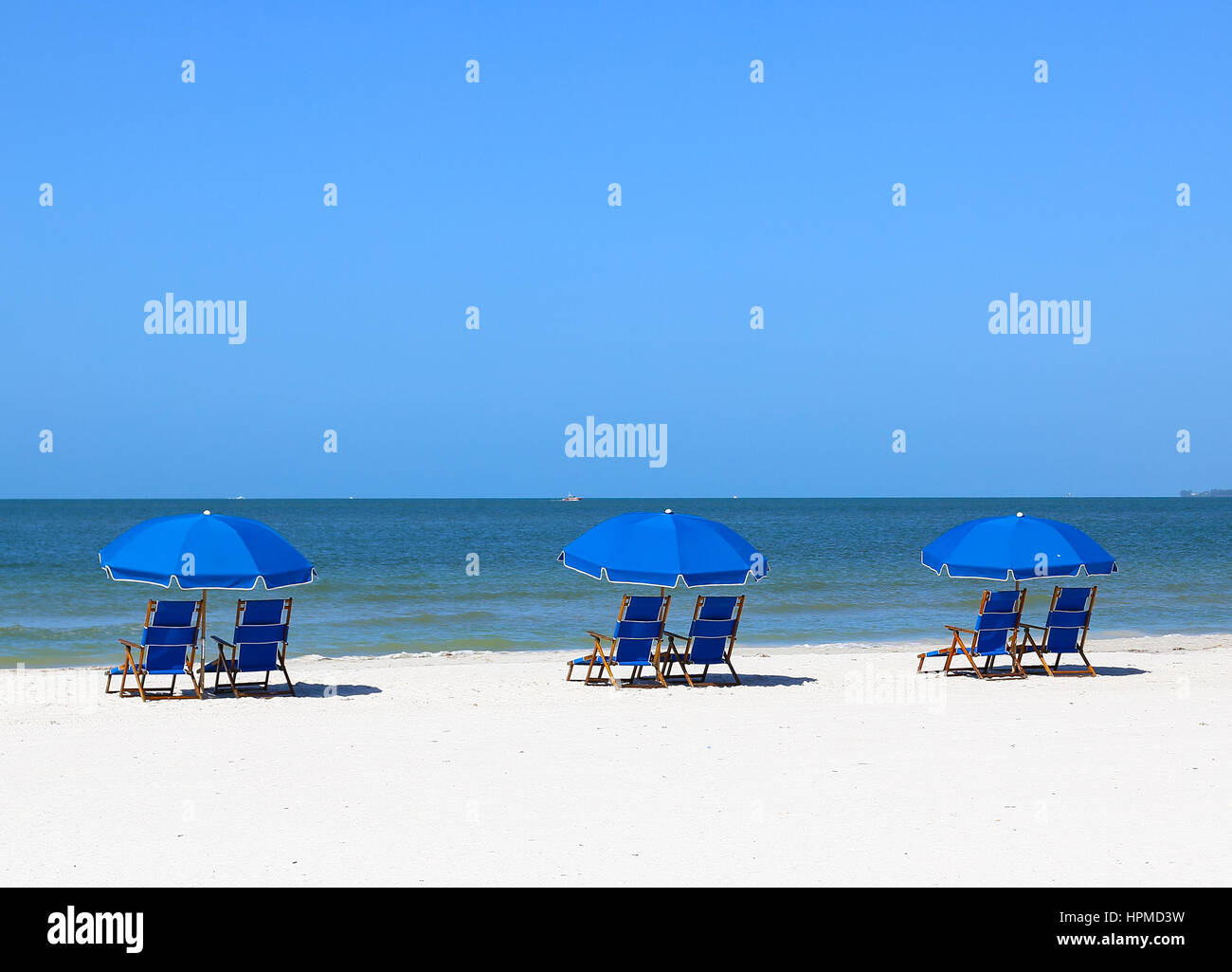 Fort Myers Beach, USA - May 12, 2015: Blue beach chairs and blue sunshades on the beach in Fort Myers Beach viewing Stock Photo