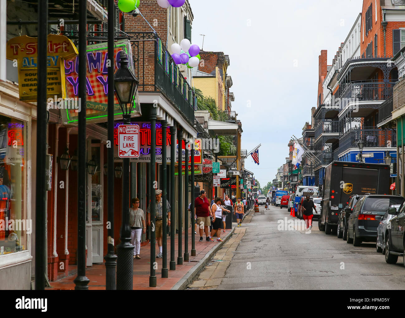 New Orleans, USA - May 14, 2015: Bourbon Street in French Quarter with pedestrians on the sidewalks and cars parked - Stock Image