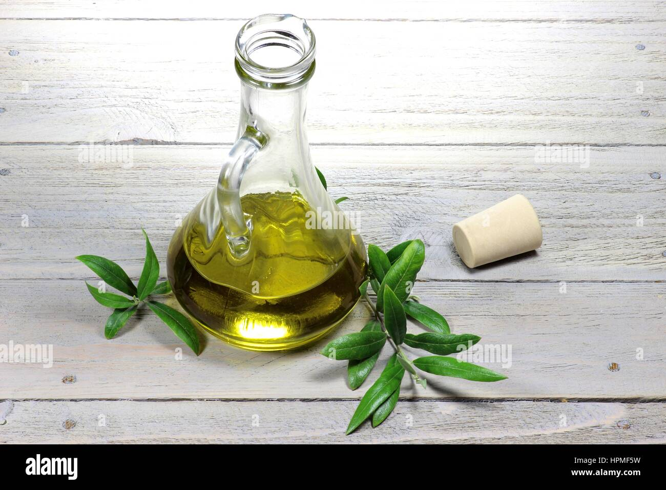 virgin olive oil in a glass carafe on wooden background - Stock Image