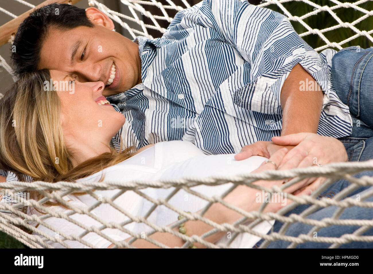 Husband embraceing his pregnant wife's belly lying in a hammock. - Stock Image