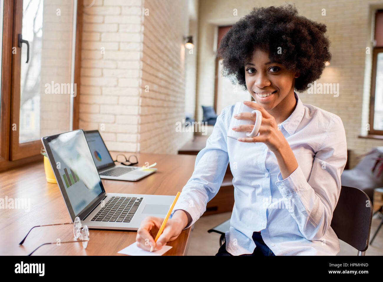 Businesswoman with coffee cup at the office - Stock Image