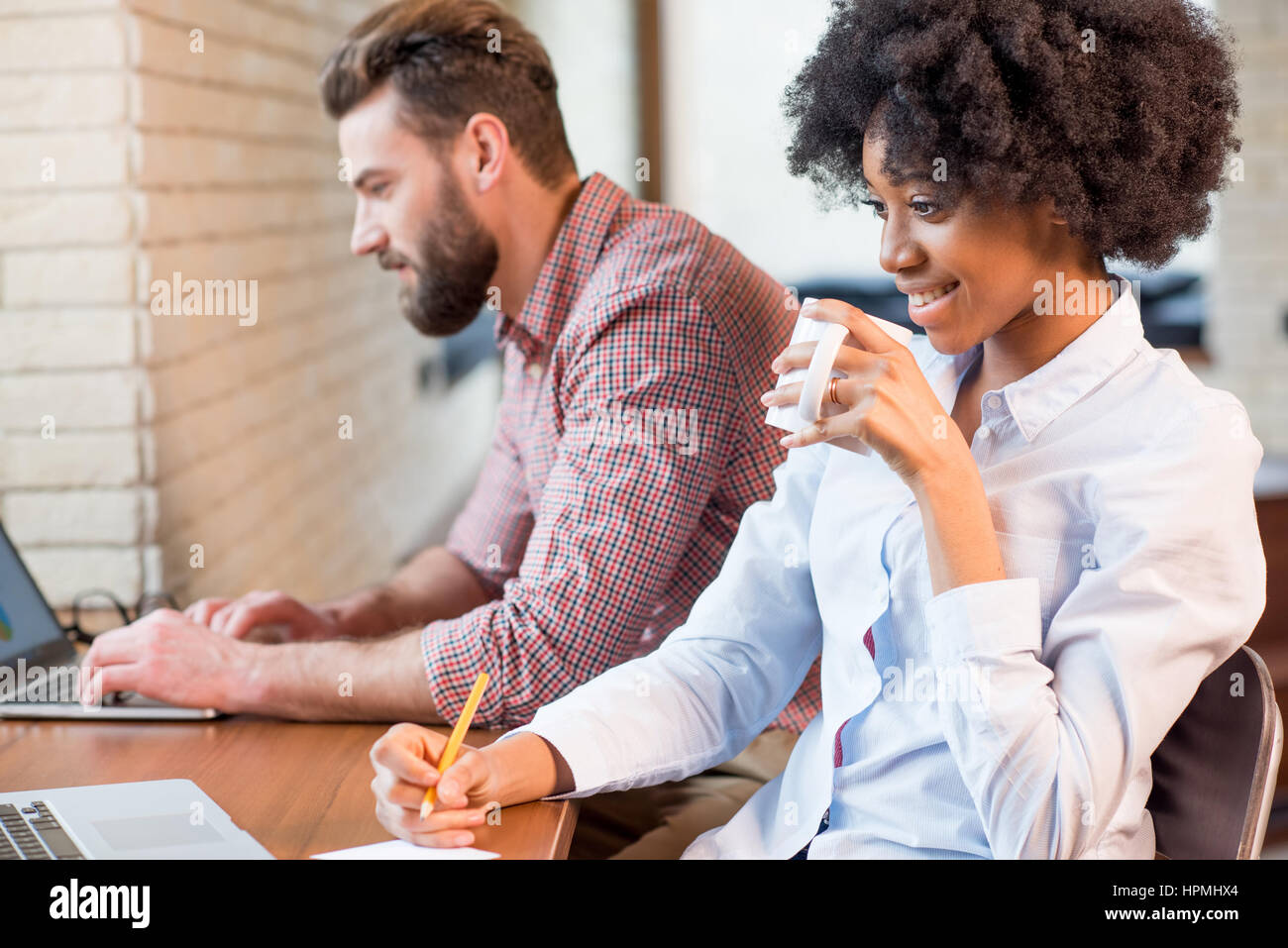 Coworkers working with laptop indoors - Stock Image