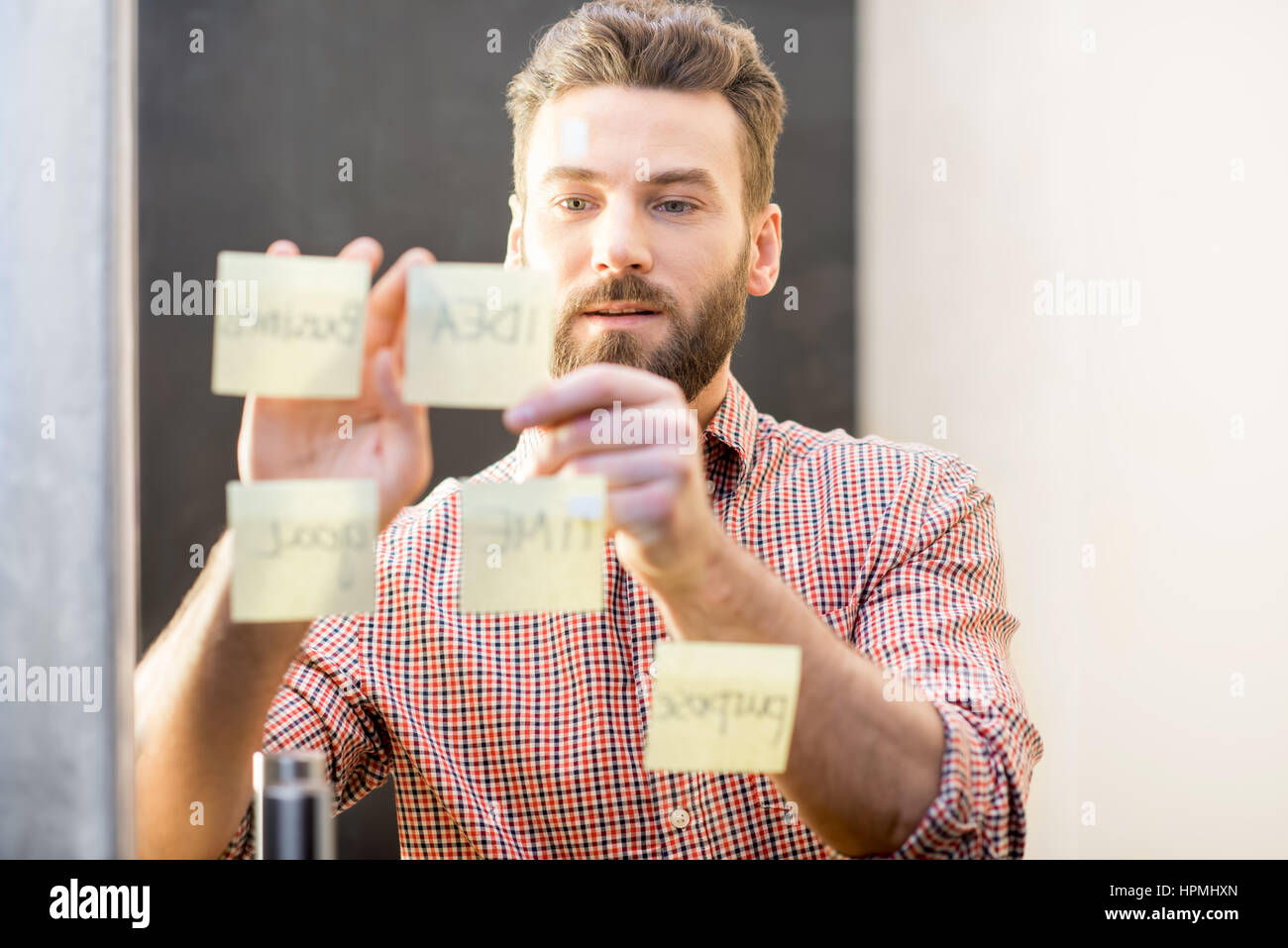 Man working with stickers on the door - Stock Image