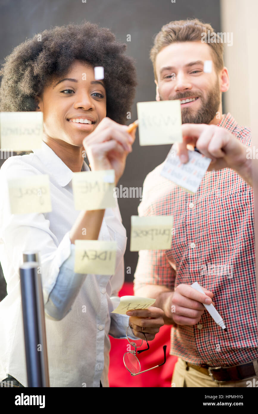 Coworkers working with stickers on the door - Stock Image