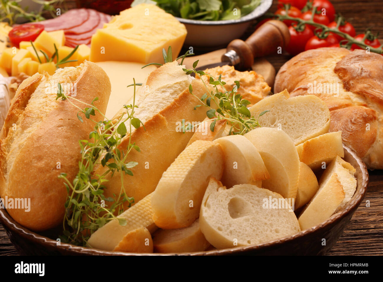 Fresh baguette and bread with herbs on rustic wooden board Stock Photo