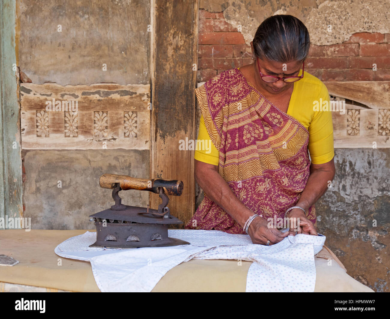 Unidentified woman in a back street in Ahmedabad, India, ironing clothes with a traditional wooden handled metal - Stock Image
