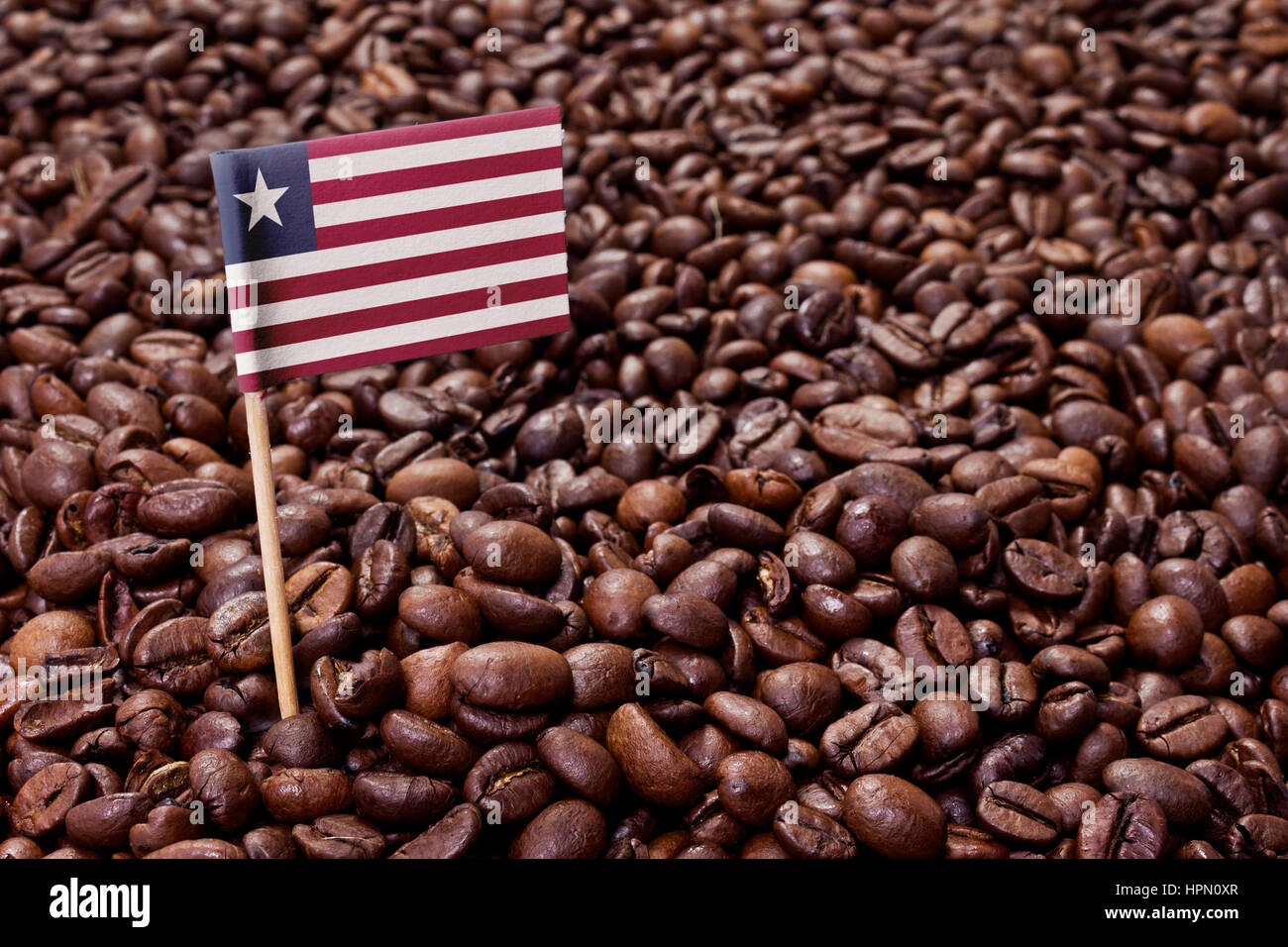 Flag of Liberia sticking in roasted coffee beans.(series) - Stock Image