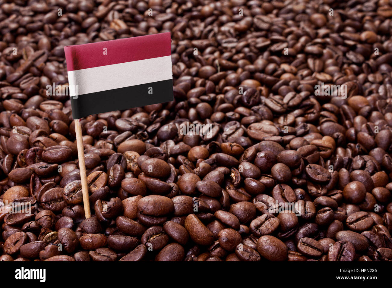Flag of Yemen sticking in roasted coffee beans.(series) - Stock Image