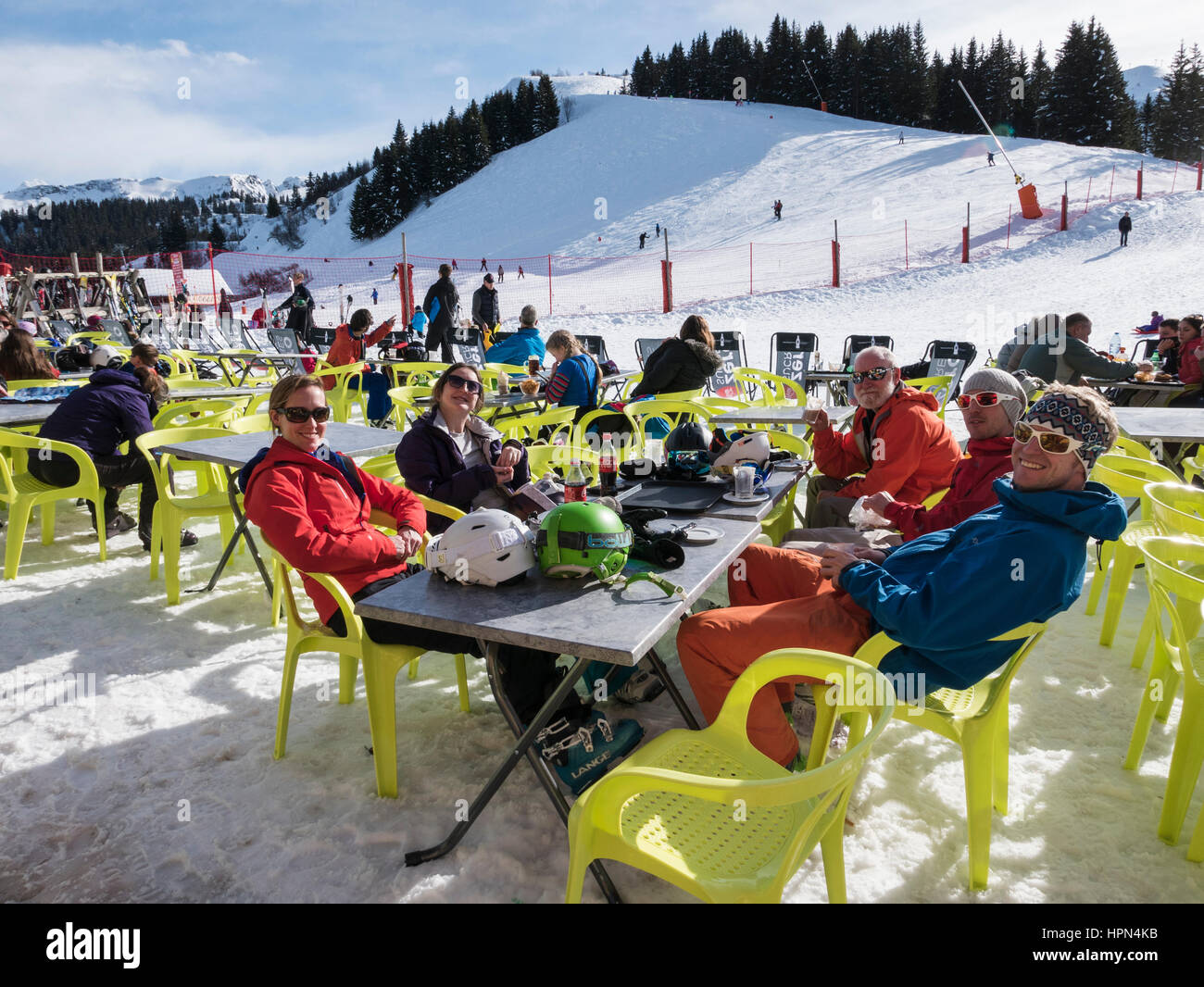 Family and friends skiers on a winter holiday enjoying sunshine dining outside a ski restaurant in French Alps. - Stock Image