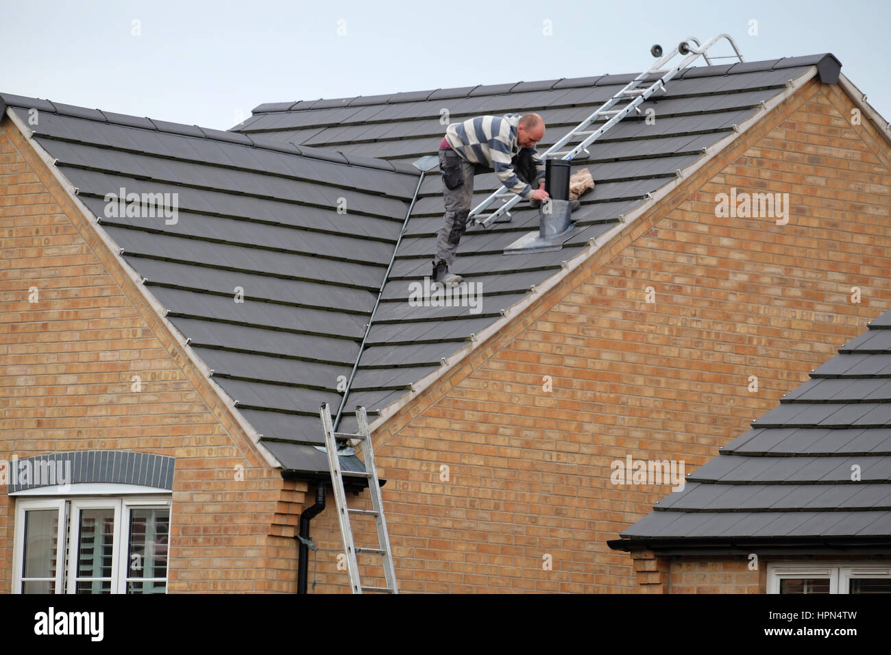 Workman on house roof installing a chimney. - Stock Image