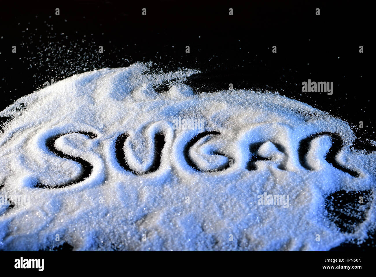 Word sugar written with finger to pile of white sugar. - Stock Image