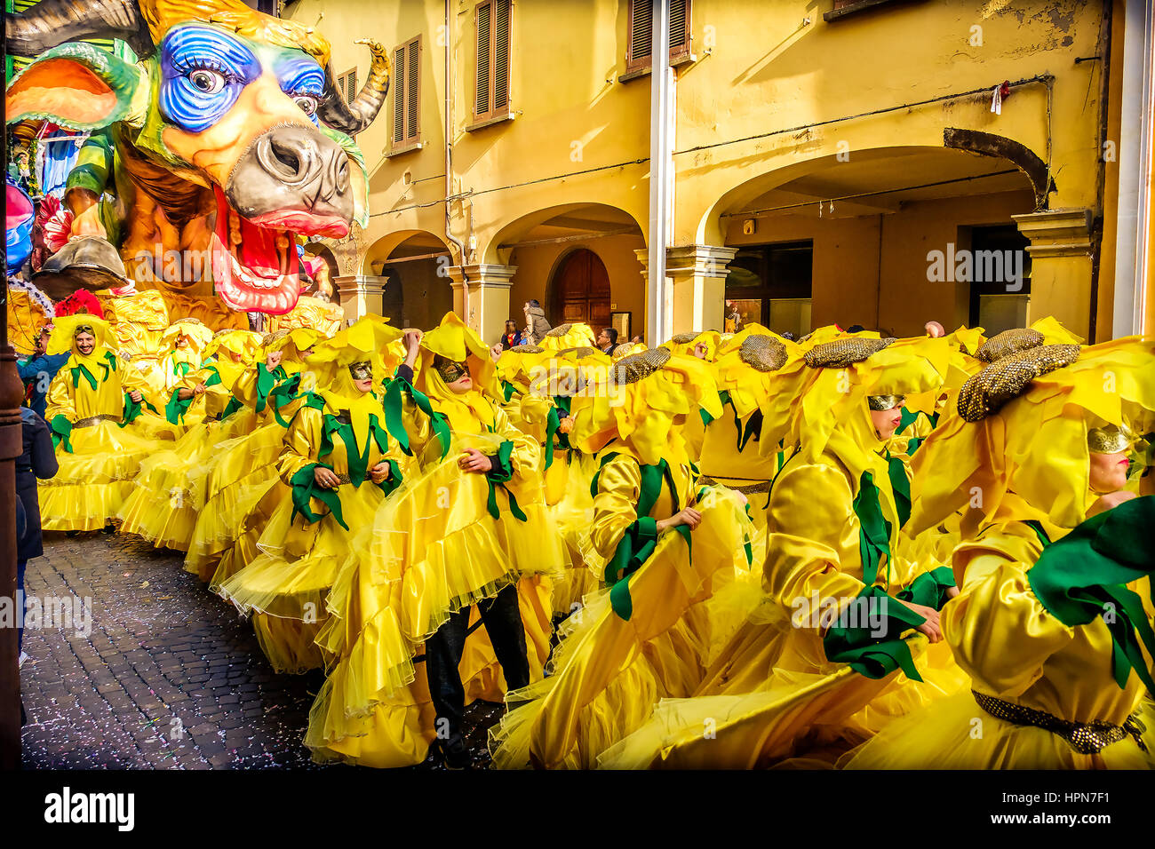 Carnevale di Cento colorful cow parade float people choreography yellow sunflower costumes - Stock Image