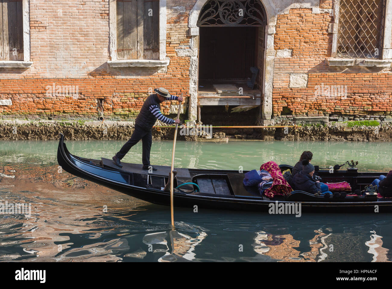 641a5de7245 A Gondolier is seen wearing the traditional Gondolier s hat whilst rowing  along an internal canal in