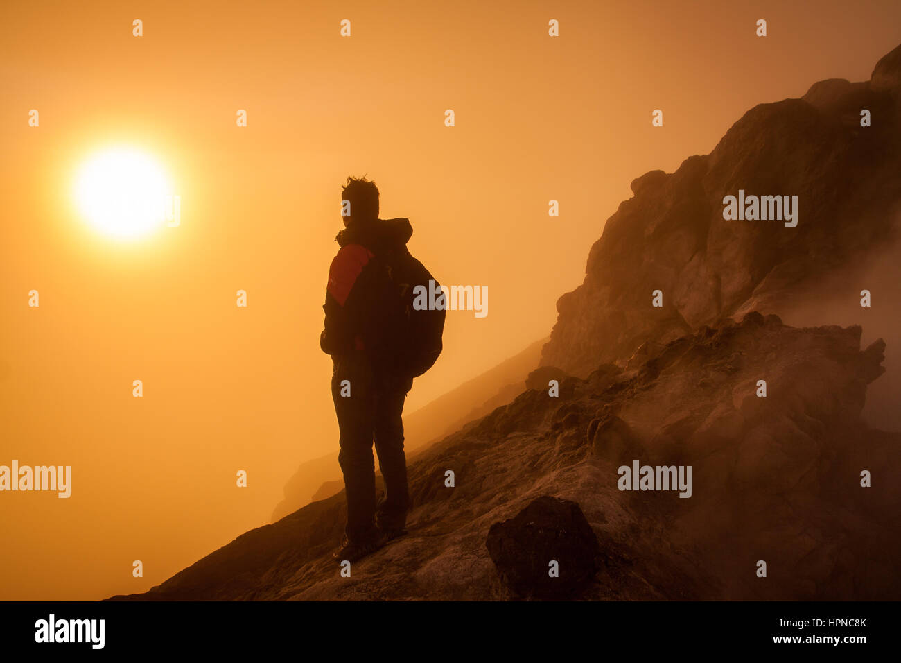 Mountain hiker watching sunrise from Mount Merapi (Gunung Merapi) volcanic crater, a highly active volcano in Indonesia - Stock Image