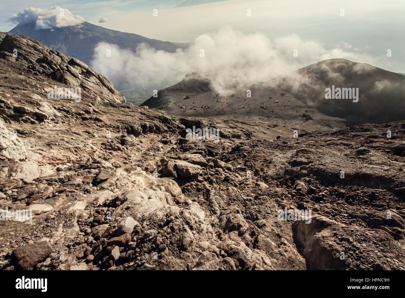 Looking down from Mount Merapi Active Volcano Crater over some treacherous volcanic rock a dangerous mountain landscape. - Stock Image