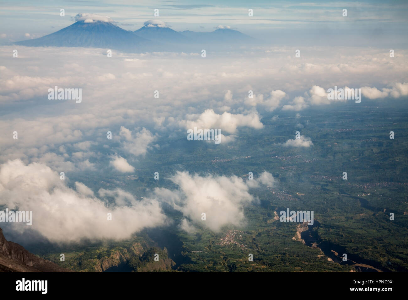 High altitude aerial view of the volcanic terrain in Central Java, Indonesia. Where volcanoes commonly rise out - Stock Image