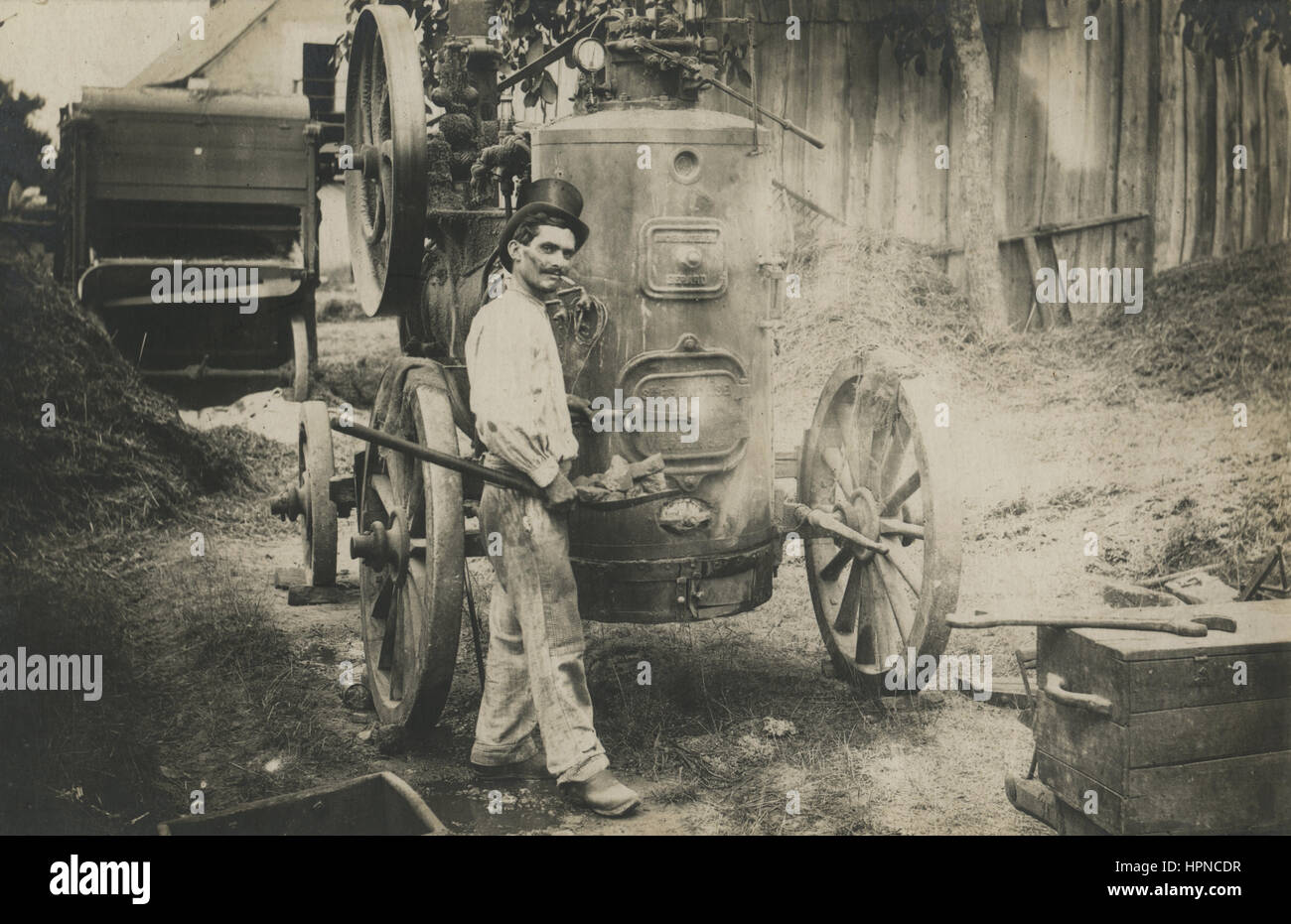Early 1900s antique Steampunk photo of an engineer, worker with a top hat loading coal in a portable steam engine - Stock Image