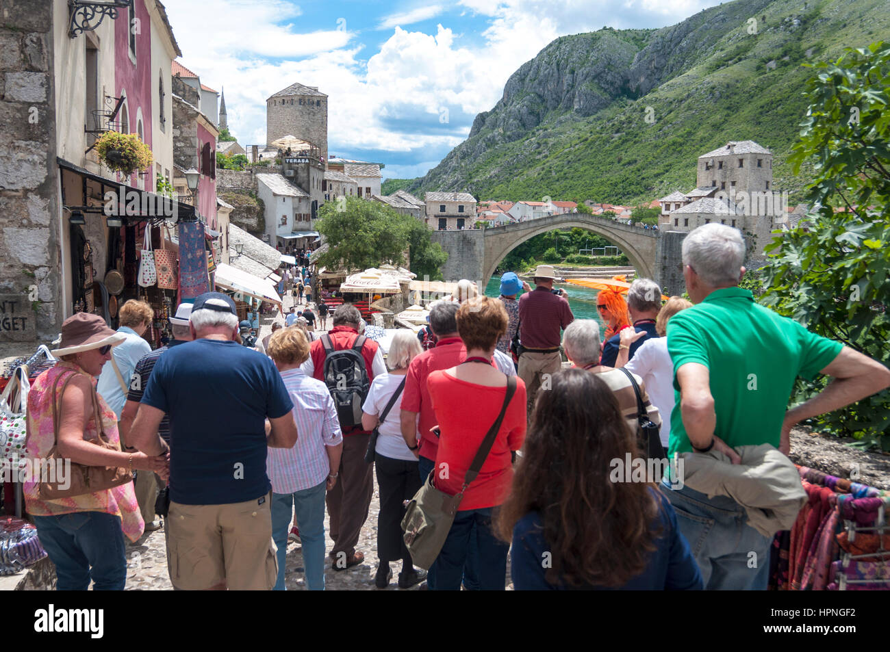 Tourists in Mostar, Bosnia Herzegovina. Looking at Stari Most old bridge in the town - Stock Image