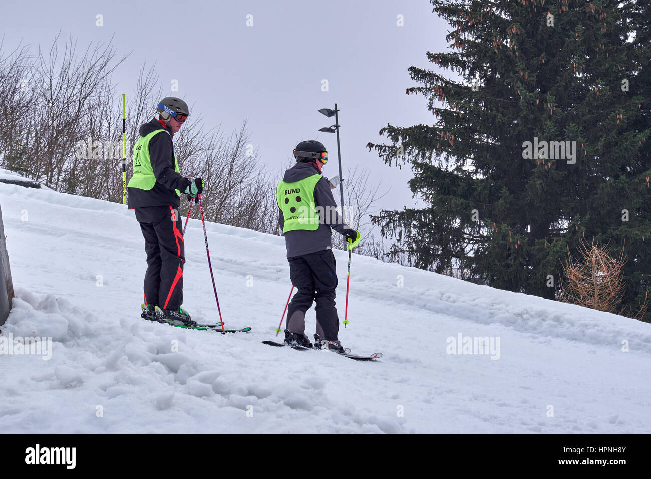 WINTERBERG, GERMANY - FEBRUARY 16, 2017: Young blind downhill skier and his helper on a piste at Ski Carousel Winterberg - Stock Image