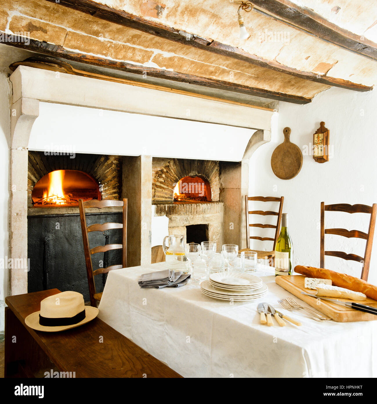 A dining table by ovens. - Stock Image