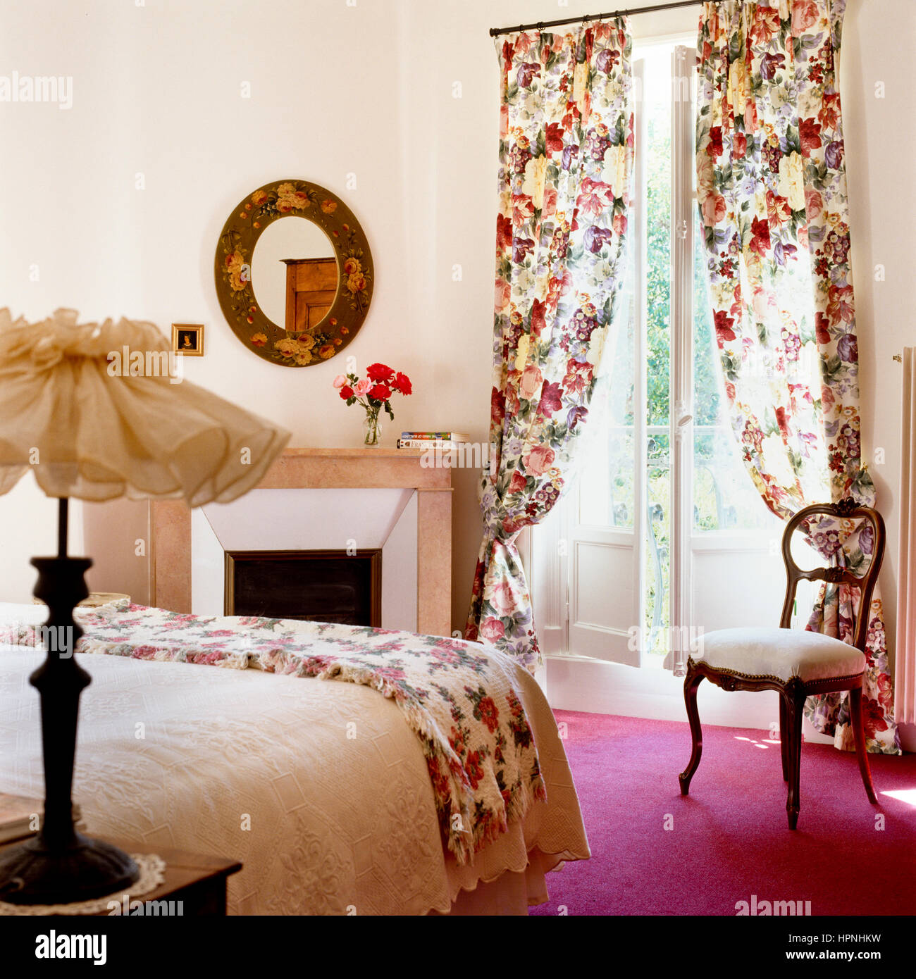 A bedroom with floral patterns. - Stock Image