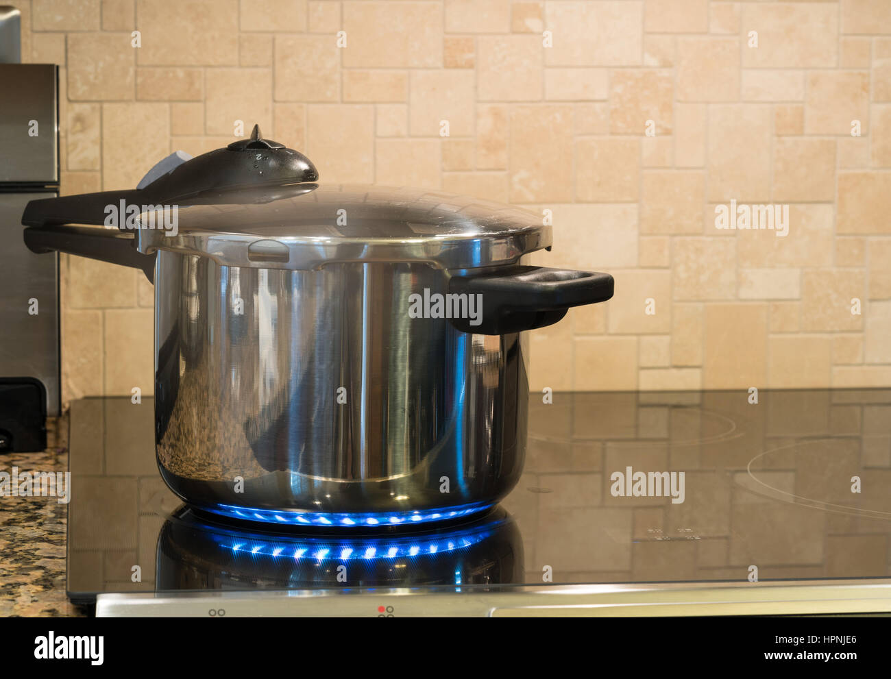 Stainless steel pressure cooker letting off steam on a modern induction cooking hob with glass top - Stock Image
