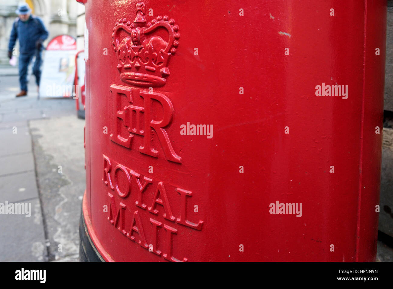 A red Royal Mail post box is pictured outside a post office in Bath,England, UK - Stock Image