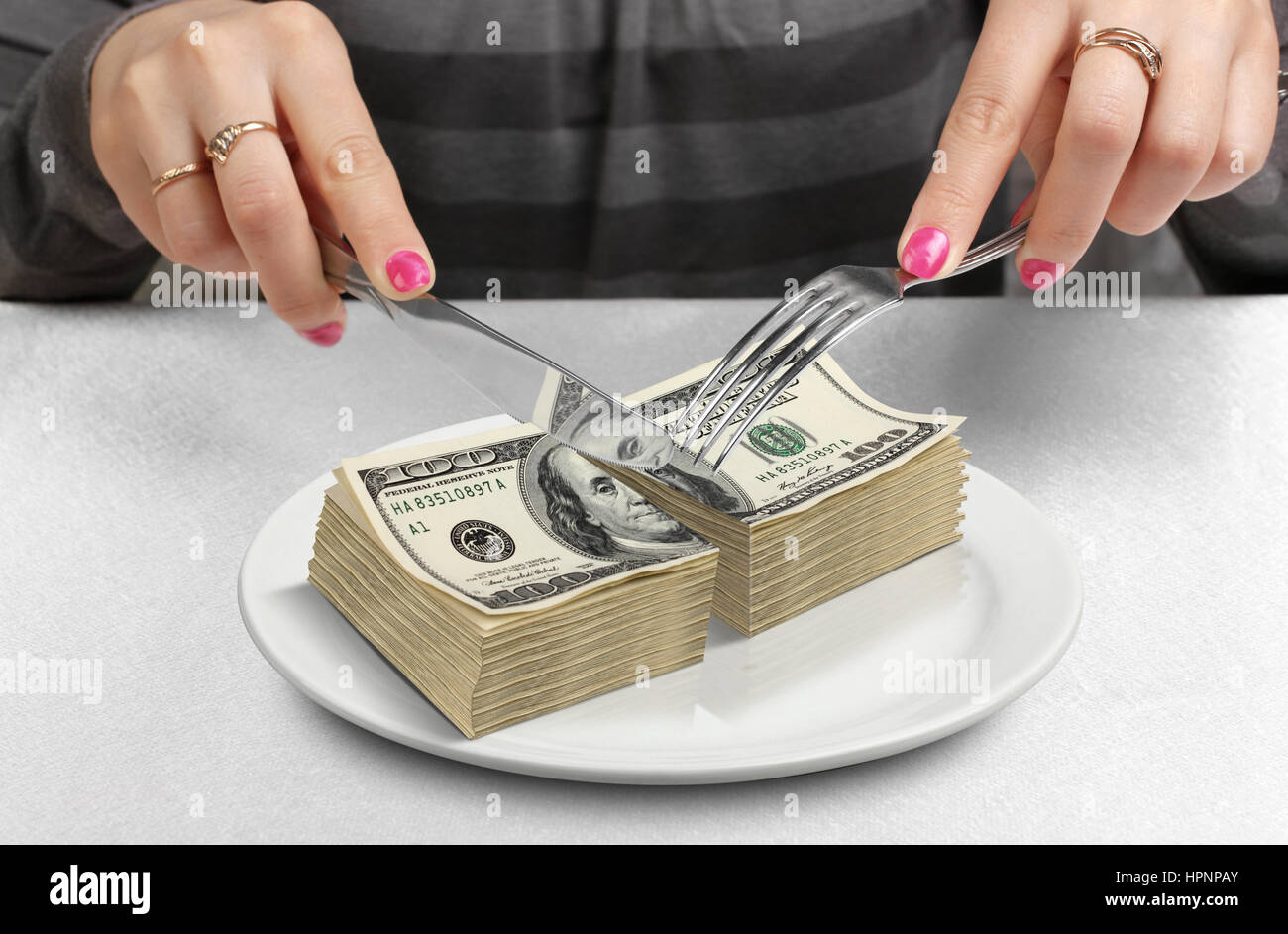 Cut money on plate, cut budget concept - Stock Image
