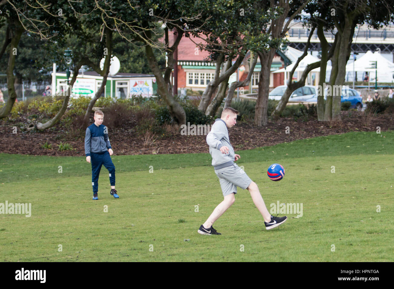 Boys enjoy a kick-around on the park next to Southport sea front during an unseasonally warm February day. 22/02/17. - Stock Image