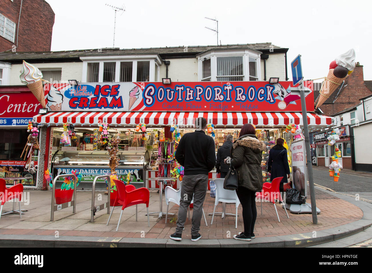 Visitors buy souvenirs and ice cream at a shop close to Southport sea front, during an unseasonally warm February - Stock Image