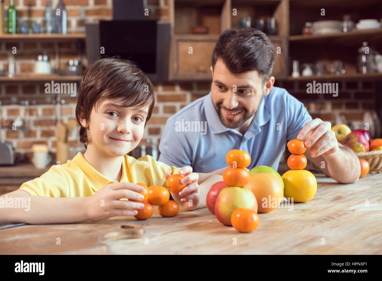 father and son playing with citrus fruits at kitchen table - Stock Image