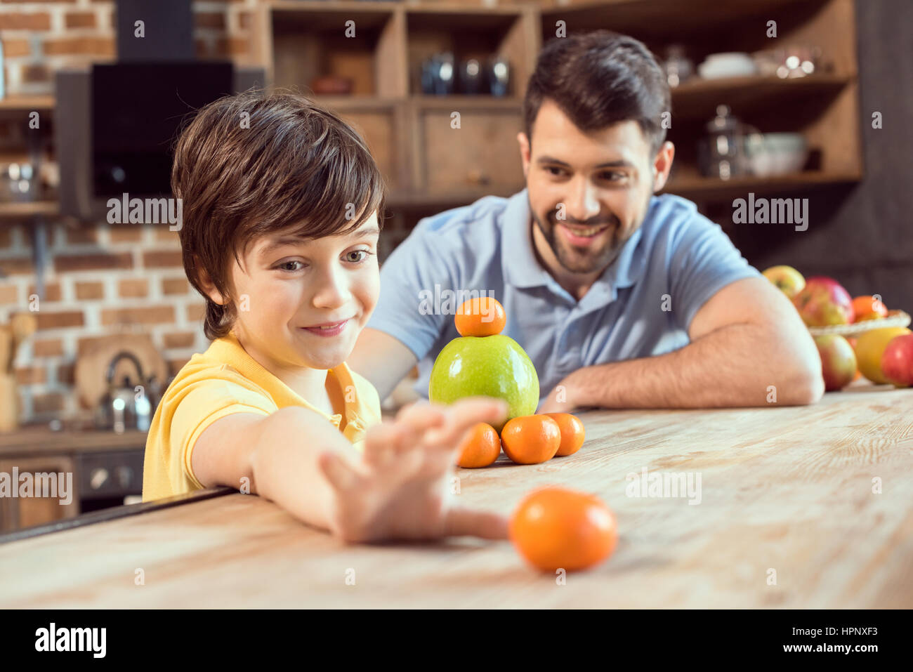 father and son playing with citrus fruits in kitchen - Stock Image