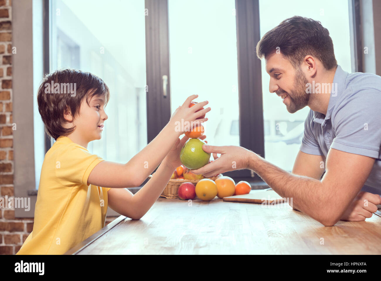 happy father and son playing with citrus fruits in kitchen - Stock Image