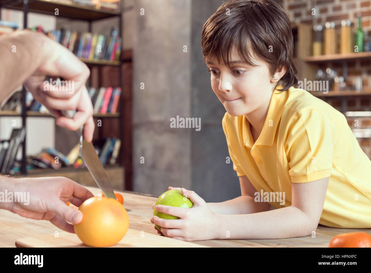 cute smiling son looking at father cutting grapefruit with knife - Stock Image