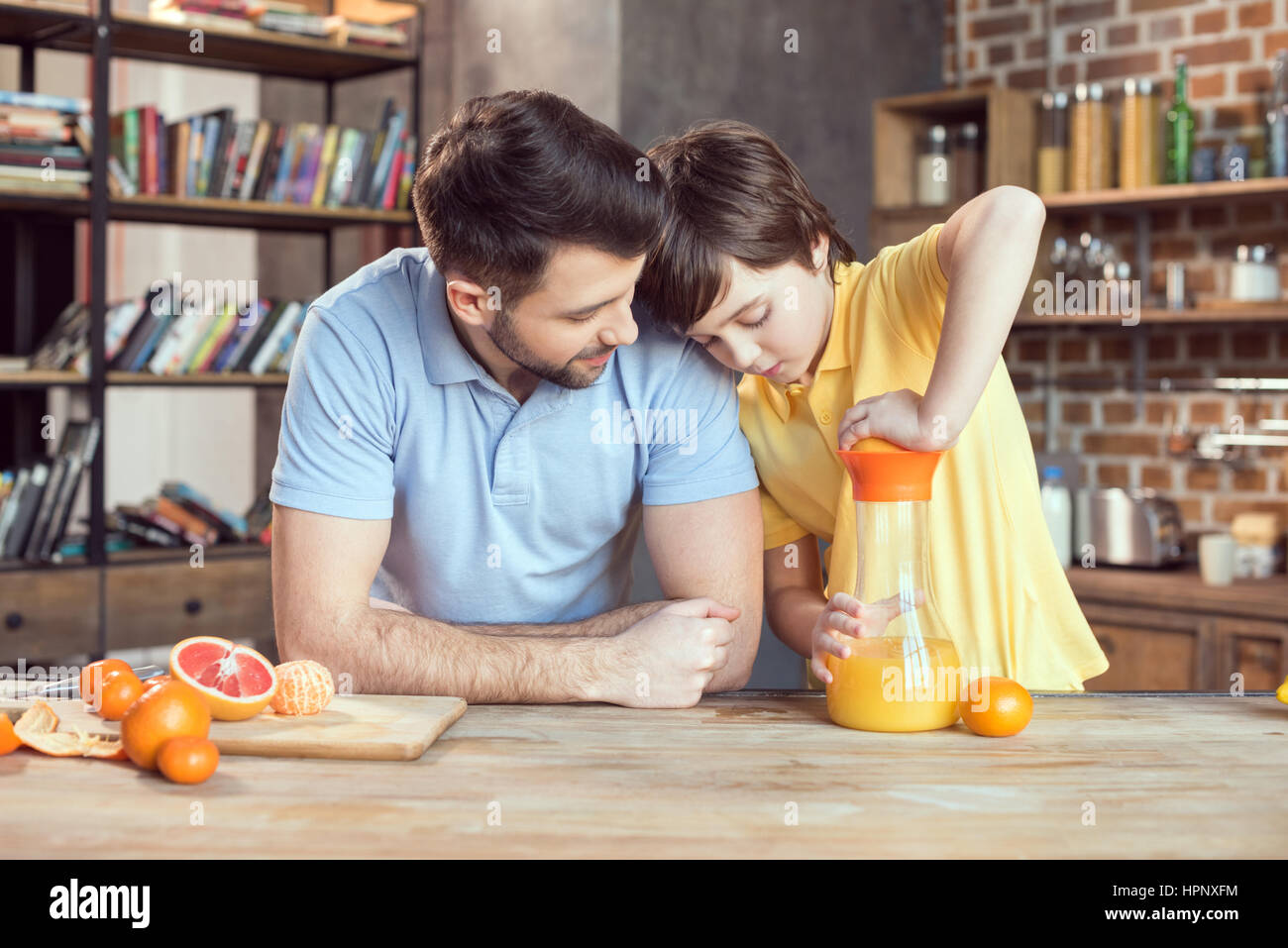 Father and son squeezing fresh orange juice - Stock Image