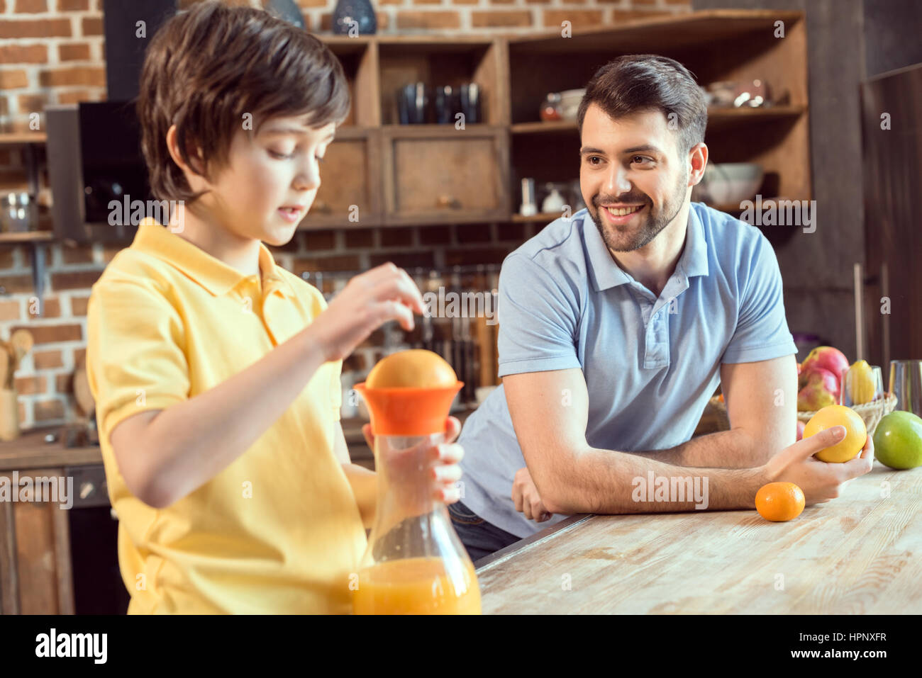father looking at little son squeezing fresh juice in kitchen - Stock Image