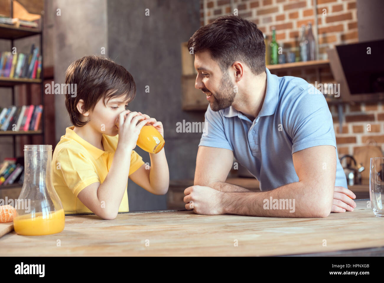 father looking at cute little son drinking fresh orange juice - Stock Image